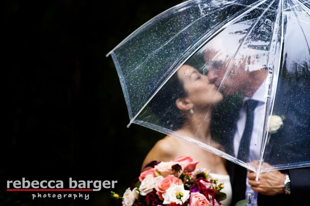 Karen + Jim have a romantic  wedding day kiss under the umbrella at Pomme, a Peachtree and Ward venue.