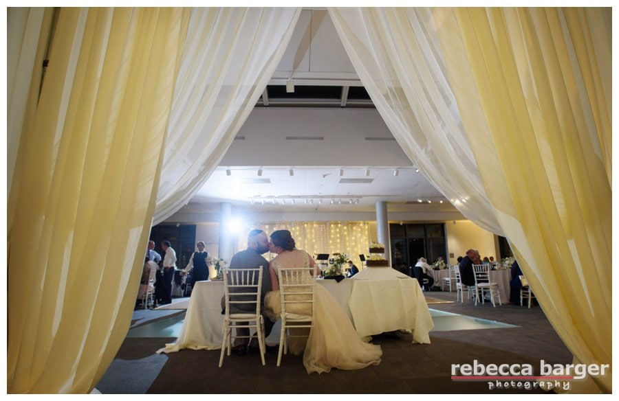 Peeking through the drapery at the newlyweds enjoying their meal at their NMAJH wedding reception. Lighting and drapery by Shipley Enterprises.