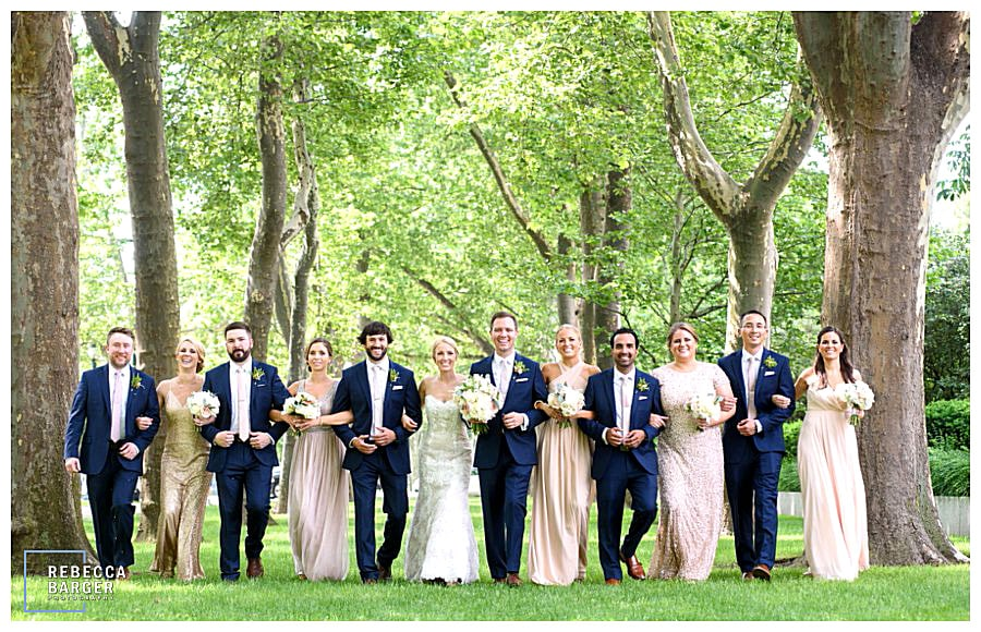 A gorgeous bridal party walking amongst the trees on the way to the wedding at The Free Library of Philadelphia, Brûlée Catering.
